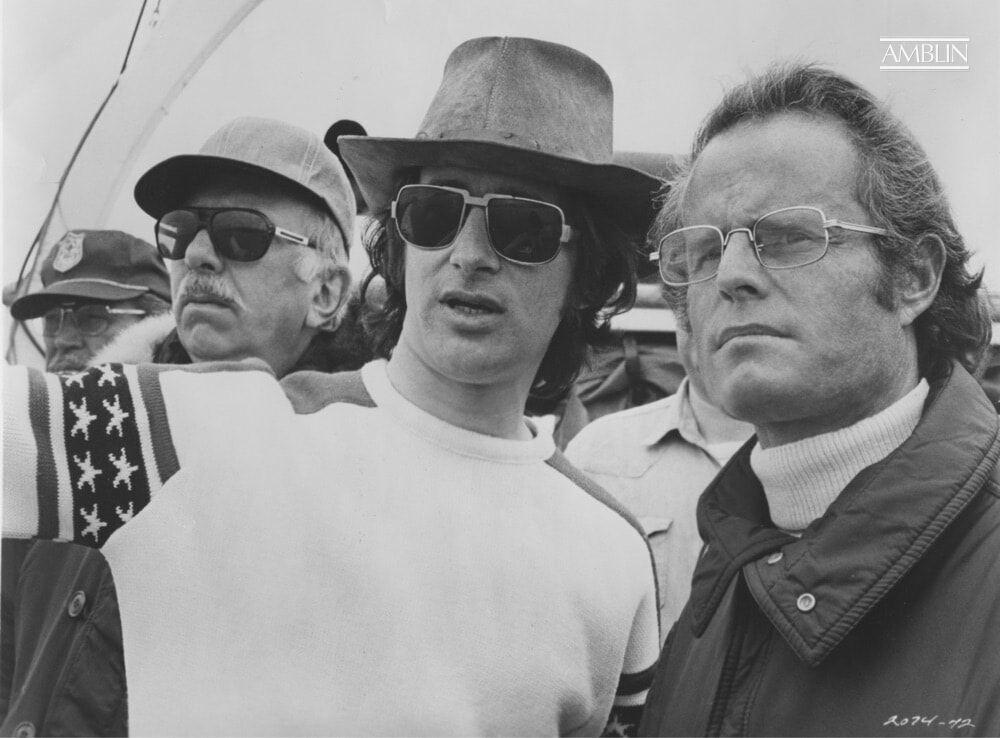 On location, discussing production details with producer Richard Zanuck. Producer David Brown can be seen directly over Spielberg's right shoulder.