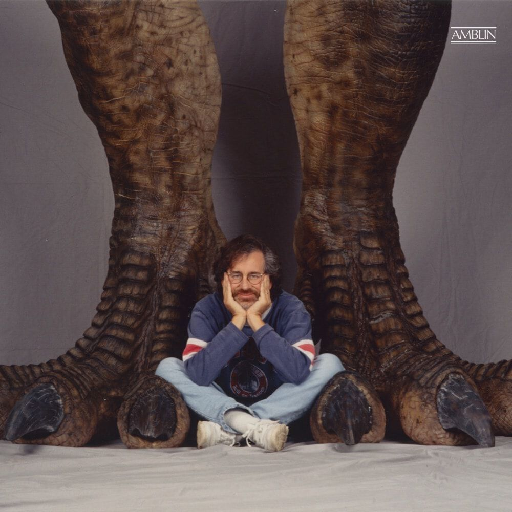 The director sits at the feet of what appears to be a 20-foot turkey, the T. rex that would terrify audiences around the globe in the Summer of 1993.