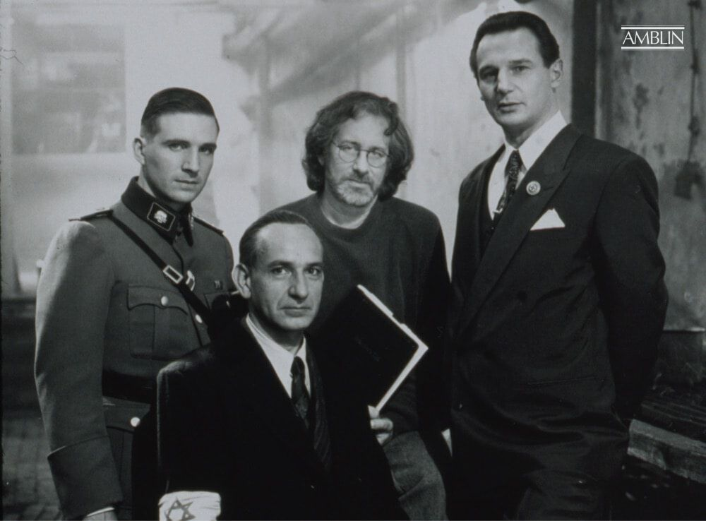 Posing with his trio of actors at the heart of the struggle in Schindler's List, (L to R) Ralph Fiennes, Sir Ben Kingsley, Spielberg and Liam Neeson. Spielberg holds a bound edition of the screenplay in hand.