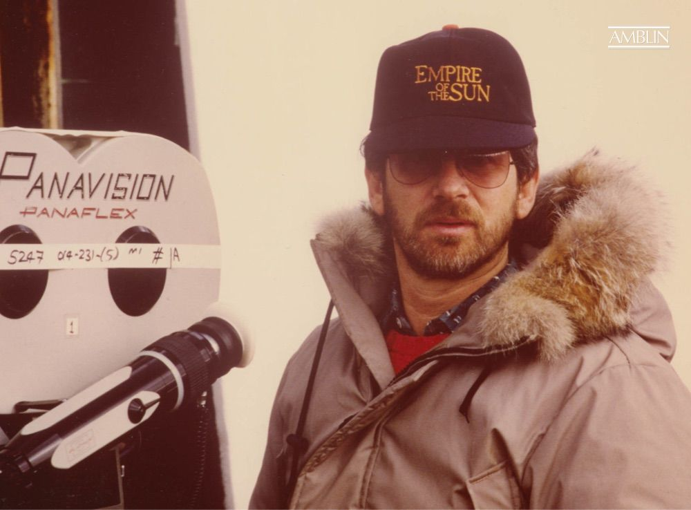 On location shooting Empire of the Sun, proudly wearing a crew hat for the film while he creates it.